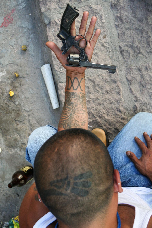 """Meeting different gangs of rough areas in San Luis Potosi, 400 km north of City of Mexico (2007-2017).  El Choy of the Tropilocos 21 wants to stop the """"crazy life"""" (""""la vida loca"""") in order to find a legal job and meet his family needs. It's difficult in Mexico to find a job wearing tattoos. On his head, the mexican eagle of """"Made in Mexico"""" and the XXI on his arm is the gang number.  Zona Centro, San Luis Potosi, SLP, Mexico - 15/03/2007. Rencontre avec des gangs de plusieurs quartiers populaires de San Luis Potosi, à 400 km au nord de la Ville de Mexico (2007-2017). El Choy des Tropilocos veut laisser de côté """"la vie folle"""" pour trouver un travail légal et subvenir aux besoins de sa famille. Il est difficile au Mexique de trouver un emploi si on porte des tatouages. Sur son crâne, l'aigle mexicain du """"Fabriqué au Mexique"""" (Hecho en México) et le XXI sur son bras est le numéro de la bande. Zona Centro, San Luis Potosi, SLP, Mexique - 15/03/2007.   Zona Centro, San Luis Potosi, SLP, Mexico - 15/03/2007."""