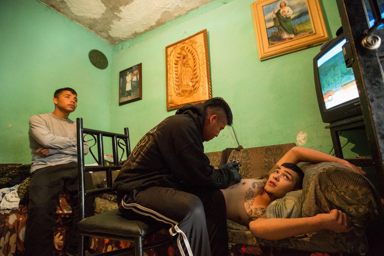 Dans le quartier del Ojo de Agua avec la bande des Millionarios. Un des jeunes de la banda se fait tatouer.           Saltillo, Coahuila, Mexique