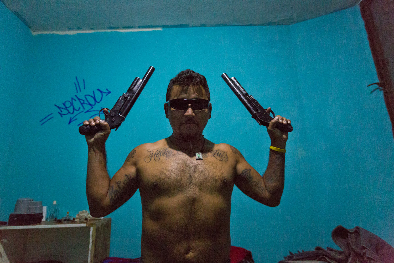 El Mijis stages with guns of the neighborhood on a cartoonish way. He refused the use any arm for a long time ago in order to work in prevention and social area in general.San Luis Potosi, Mexico - 10/12/2015.El Mijis pose avec des armes du quartier de manière caricaturale. Ça fait bien longtemps qu'il s'est refusé à leur utilisation pour notamment travailler dans la prévention et le travail social en général.San Luis Potosi, Mexique - 10/12/2015.