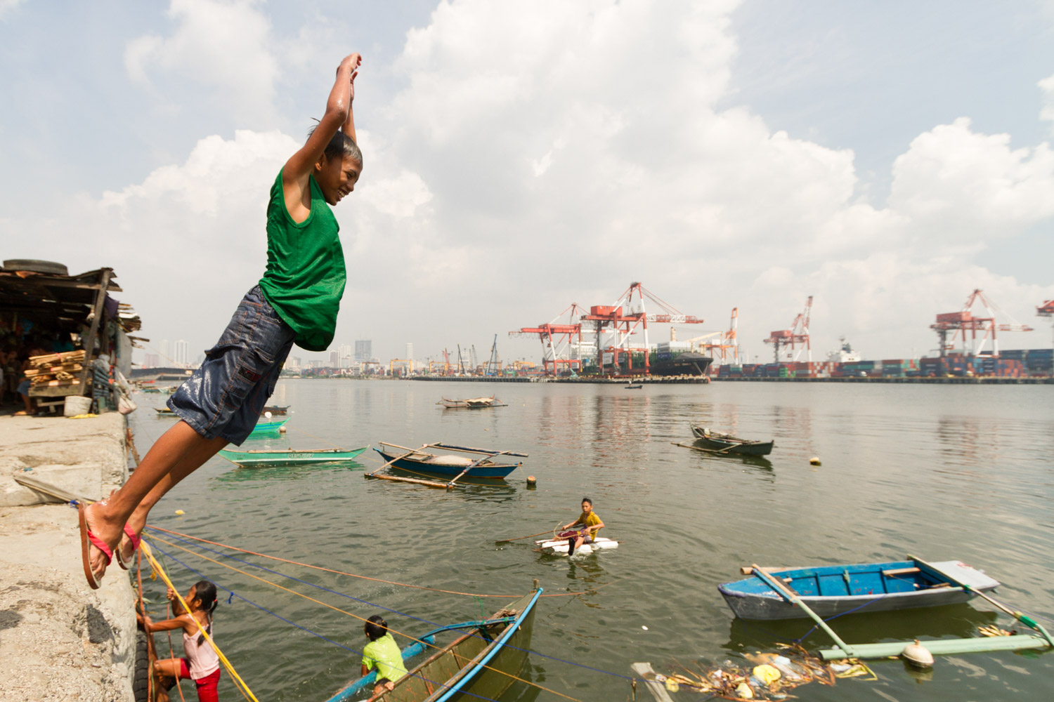 Baseco is an informal neighborhood of Manila located between the international port and the Pasig river. More than 50 000 people are living there in very precarious conditions. Children are playing and jumping in the contaminated water of the international port. Baseco, Manila, Metro Manila, Philippines - 18/10/2012.
