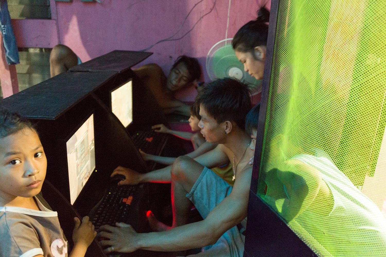 Eman joue aux jeux vidéo dans le garage de la maison familiale. Les jeux vidéo sont très populaires pour les jeunes du quartier.