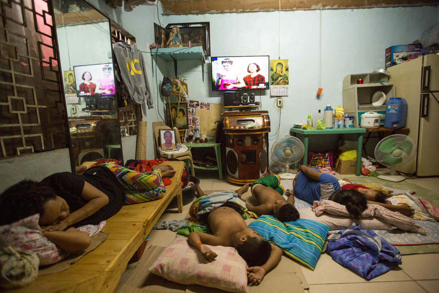 Baseco is an informal neighborhood of Manila located between the international port and the Pasig river. More than 50 000 people are living there in very precarious conditions. All the family got sleeping watching the TV. On a chair on the left of the screen is a picture of the father, who got shot in his shop getting stolen the cash. Manila, Philippines - 13/01/2016.