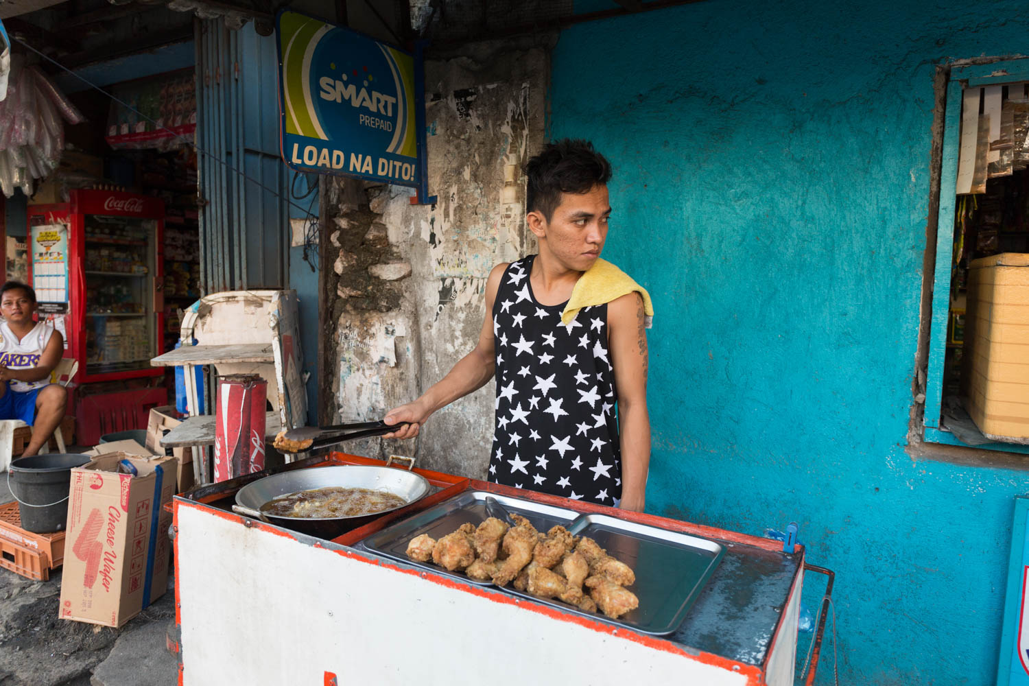 In the main street of Buli, in Muntinlupa, a young boy is selling chicken legs with breadcrumbs.Buli, Muntinlupa, Metro Manila, Philippines - 12/01/2016.