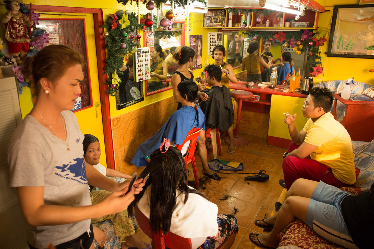"""Baseco is an informal neighborhood of Manila located between the international port and the Pasig river. More than 50 000 people are living there in very precarious conditions. The """"Montemayor Sisters"""" in their hair salon, located in the main avenue of Baseco. Manila, Philippines - 13/01/2016."""