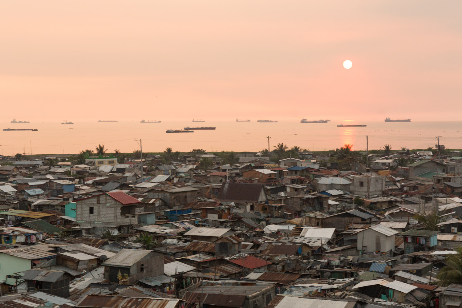 Baseco is an informal neighborhood of Manila located between the international port and the Pasig river. More than 50 000 people are living there in very precarious conditions.  Sunset on Baseco and Manila bay. Many boats are waiting to enter to the port. Manila, Philippines - 13/01/2016.