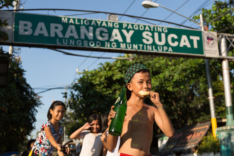 Un enfant du quartier de Buli pose devant le panneau annonçant le quartier voisin de Sucat