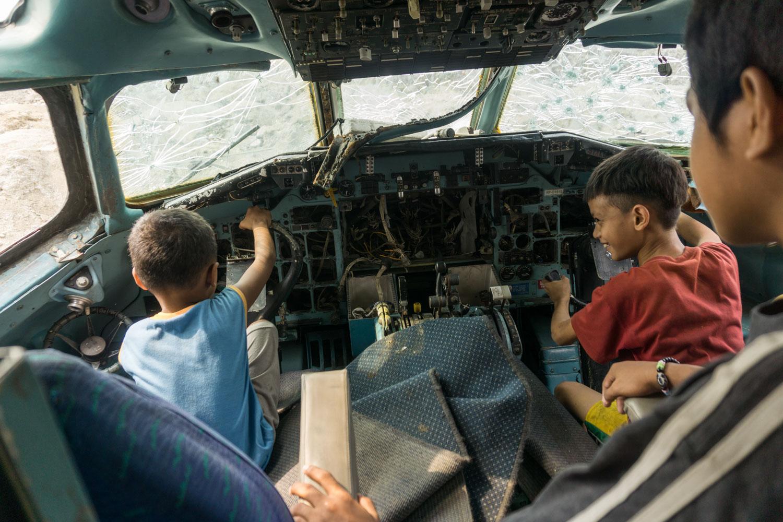 Paranaque, Grand Manille, Philippines. Des enfants jouent dans le cockpit d'un avion abandonné sur un terrain proche de chez eux.