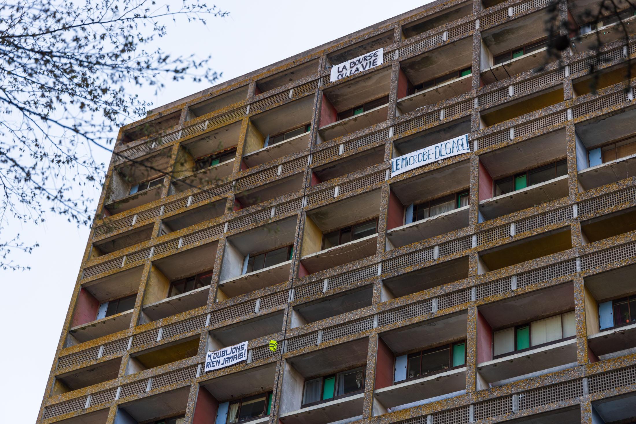 """Residents of the radiant city of Corbusier posted banners on their balconies, such as """"Microbe fuck off!"""". Reze, France - April 2nd 2020.Des habitants de la cite radieuse du Corbusier ont affiche des banderoles sur leurs balcons, comme """"le microbe, degage!"""". Reze, France - 2 avril 2020."""